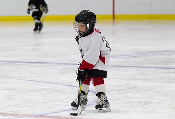 young boy preparing for ice hockey