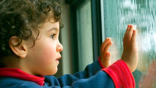 a young child looks longingly out the classroom window as it rains