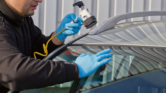 Technician installing auto glass replacement